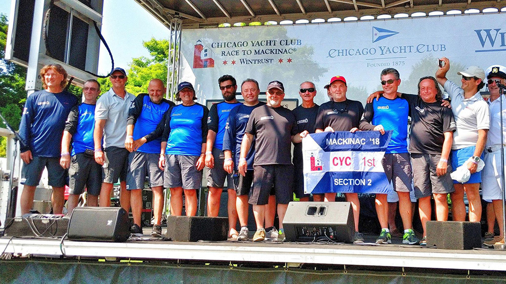 The crew of the sailing vessel Husaria accept the first place award for section 2 in the Mac Race