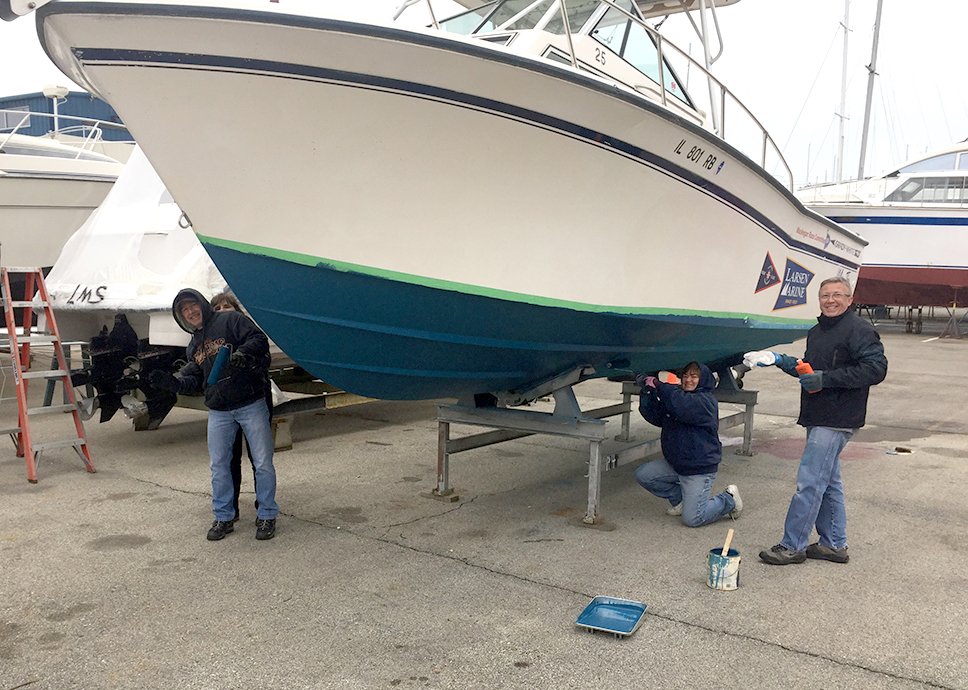 members painting the club's boats