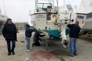 volunteers sand and paint the committee boat