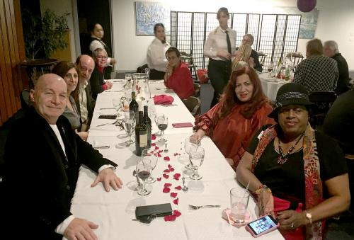 large table of smiling guests waiting to be served